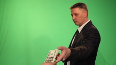 A man in a business suit takes another person's dollars. Stock Footage