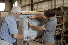 Father watching son restore boat in workshop - stock photo