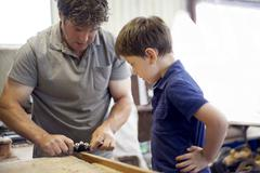 Father showing son carpentry in boat  workshop - stock photo