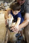 Father mentoring son on carpentry in boat  workshop Stock Photos