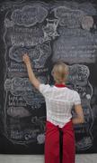 Waitress writing on blackboard menu in cafe - stock photo