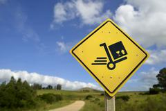 Shipping concept delivery box cart on road sign Stock Photos