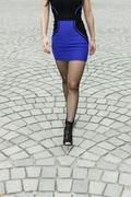 Waist down shot of woman wearing dress and boots walking across paved street - stock photo
