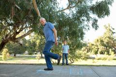 Grandfather on hopscotch, boy watching - stock photo