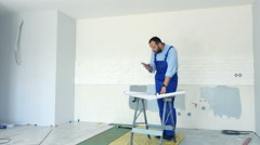 Male worker working with smartphone and blueprints during renovation at new home Stock Footage