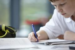 Close up of schoolboy writing in class Stock Photos