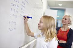 Schoolgirl doing multiplication on white board Stock Photos