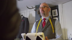 4K Customer making payment with a credit card in a man's clothing store.  Stock Footage
