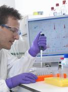 Male scientist pipetting sample into test tubes for analysis of cell population Kuvituskuvat