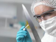 Forensic scientist in laboratory taking DNA evidence with a swab for crime Stock Photos