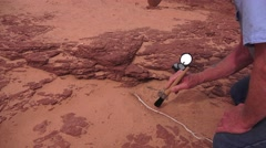 Archeologist sweep sand from fossil turtle Stock Footage