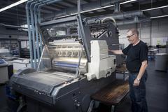 Worker operating print machine in printing workshop Stock Photos