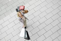Portrait of mid adult woman with abundance of shopping bags - stock photo