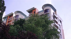 Modern multistorey building among trees, nice place to live, establishing shot Stock Footage