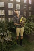 Mid adult man with harvested beetroot on council estate allotment - stock photo