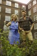 Couple watering vegetables on council estate allotment - stock photo