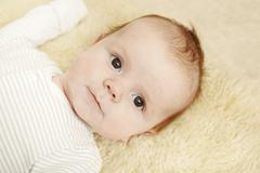 Two month old baby boy lying on furry blanket - stock photo