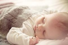 Two month old baby boy asleep in crib - stock photo