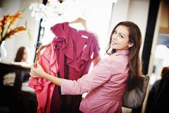 Young woman looking pink top on hanger Stock Photos