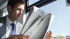 4k Businessman reading newspaper and drinking coffee on train journey Stock Footage
