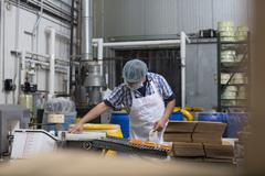 Man packaging vegan cheese in warehouse Stock Photos