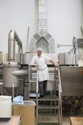 Man standing on steps in food production factory Stock Photos
