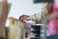 Senior woman looking through filing cabinet Kuvituskuvat