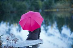 Woman with pink umbrella by lake, Bellingham, Washington, USA Stock Photos