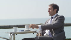 4k Businessman relaxing and drinking coffee at seafront cafe - stock footage
