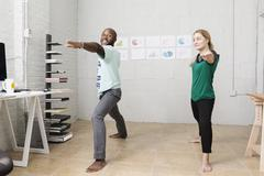 Young business partners doing exercises in design office - stock photo