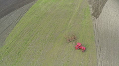 AERIAL, Old red Tractor plowing Agricultural field in countryside landscape Stock Footage