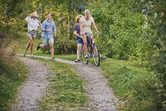 Two young couples chasing each other along dirt track, Gavle, Sweden Stock Photos