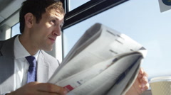 4k Businessman reading newspaper and drinking coffee on train journey - stock footage