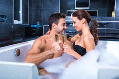 Beautiful young couple drinking Champagne in the Whirlpool - stock photo