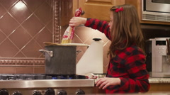 A girl pouring spaghetti noodles into a pot of water on the stove Stock Footage