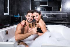 Beautiful young couple drinking Champagne in the Whirlpool Stock Photos