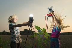 Brother and sister generating light from wind power, Zeeland, Netherlands - stock photo