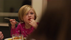 Close up on a little girl eating dinner with her family Stock Footage