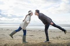 Young couple on one leg, Brean Sands, Somerset, England - stock photo