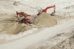 Excavators in sand - stock photo