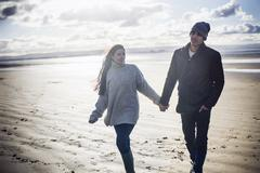 Young couple holding hands, Brean Sands, Somerset, England Stock Photos