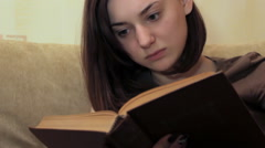 Beautiful girl turns the pages in the book Stock Footage