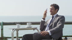 4k Businessman talking on mobile phone and drinking coffee at seafront cafe - stock footage