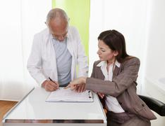 Healthcare professionals discussing medical records Stock Photos
