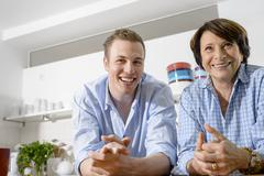 Portrait of youthful grandmother with grandson in kitchen Stock Photos