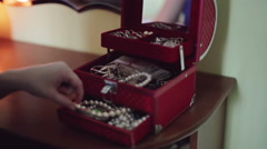 Female hands is opening red box for jewelry, and taken out of the box pearl bead Stock Footage