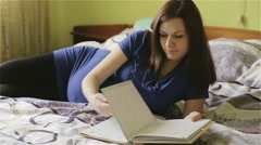 Expectant mother is lying on a bed with photo album in hands. - stock footage
