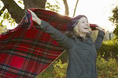 Portrait of young woman in park, holding up tartan picnic blanket Stock Photos