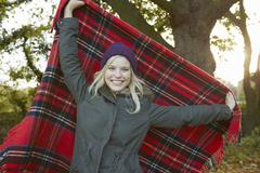 Portrait of young woman in park, holding up tartan picnic blanket - stock photo
