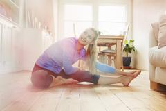 Young woman sitting on floor wearing sports clothing, stretching - stock photo